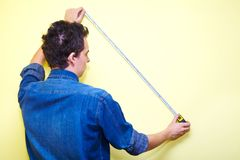 Contractor plasterer. Mature contractor plasterer working indoors in yellow room Royalty Free Stock Photography