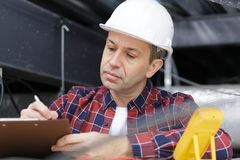 Mature contractor writing on clipboard stock photo