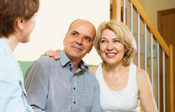 Mature couple and adult daughter  gossiping at home Stock Photos