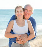 Mature couple against sea in summer Stock Photos