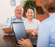 Mature couple answer questions of outreach worker. Mature couple answer questions of agent with notebook in  office Stock Photography
