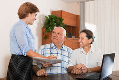 Mature couple answer questions of outreach worker Stock Photos