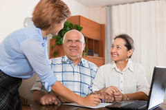 Mature couple answer questions of outreach worker. Mature couple answer questions of social worker with notebook in  office Royalty Free Stock Photo