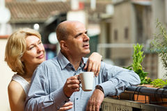 Mature couple on balcony with coffee Stock Images