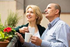 Mature couple on balcony with coffee stock image