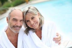 Mature couple with bathrobe sitting near pool. Happy senior couple in bathrobe by resort pool royalty free stock photos