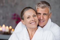 Mature couple in bathrobe at spa. Portrait of mature married couple embracing with bathrobe and looking at camera. Happy senior man and beautiful woman in robes royalty free stock images