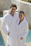 Mature Couple In Bathrobe Standing By Pool Royalty Free Stock Image