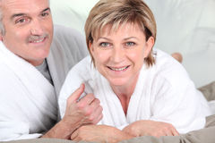 Mature couple in bed with bathrobe Stock Photos
