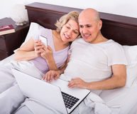 Mature couple in bed with laptop Stock Image