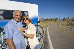 Mature couple by bicycles on back of motor home, smiling, portrait Royalty Free Stock Images