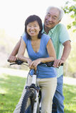 Mature couple bike riding. Mature couple bike riding in a park stock photo