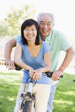 Mature couple bike riding. Mature couple bike riding in a park royalty free stock photo