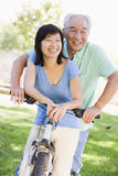 Mature couple bike riding. In a park royalty free stock image