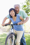 Mature couple bike riding. Mature couple bike riding in a park royalty free stock images