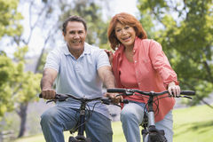 Mature couple bike riding. Mature couple bike riding on a sunny day royalty free stock photo