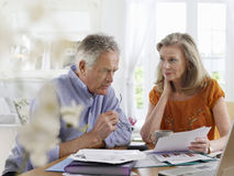 Mature Couple With Bills At Dining Table Royalty Free Stock Photos