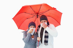 Mature couple blowing their noses under umbrella Royalty Free Stock Image