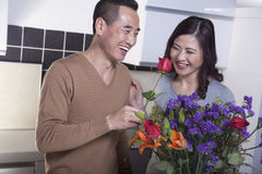 Mature Couple with Bouquet of Flowers, Man Holding a Rose Royalty Free Stock Images