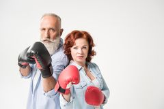 Mature couple in boxing gloves. Confident mature couple in boxing gloves, isolated on white Royalty Free Stock Photos