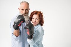 Mature couple in boxing gloves. Serious mature couple in boxing gloves, isolated on white Royalty Free Stock Photos