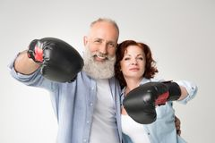 Mature couple in boxing gloves. Smiling mature couple in boxing gloves, isolated on white Royalty Free Stock Photography