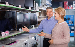 Mature couple buy in shop of household appliances TV Royalty Free Stock Image