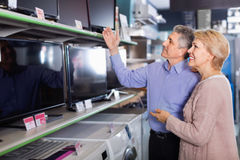 Mature couple buy in shop of household appliances TV Royalty Free Stock Photos