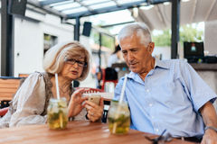 Mature Couple In Cafe Using Technology Royalty Free Stock Images