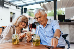 Mature Couple In Cafe Using Technology Stock Images