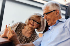 Mature Couple In Cafe Using Technology Royalty Free Stock Photo