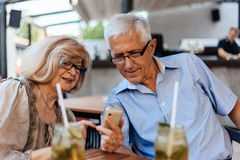 Mature Couple In Cafe Using Technology Stock Image