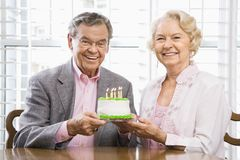 Mature couple with cake. Mature Caucasian couple holding birthday cake looking at viewer Stock Images