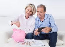 Mature couple calculating coin in the piggybank Royalty Free Stock Photos