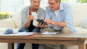 Mature couple calculating their domestic bills Royalty Free Stock Photos