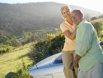 Mature couple by car in countryside, smiling, portrait Royalty Free Stock Image