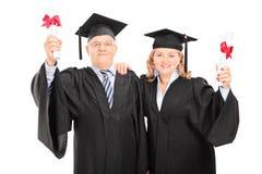 Mature couple celebrating their diplomas Royalty Free Stock Image