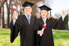 Mature couple celebrating their diplomas in park Royalty Free Stock Photography