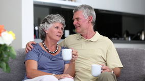 Mature couple chatting together with a cup of coffee on a sofa stock footage