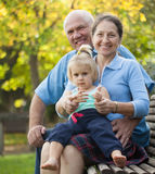 Mature couple with child sitting on bench Stock Photo