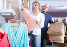 Mature couple choosing apparel in store. Portrait of happy mature couple choosing new apparel in clothing shop Stock Images