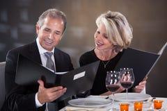 Mature couple  choosing menu. Mature Couple Sitting In Restaurant Woman Choosing Menu Royalty Free Stock Photo