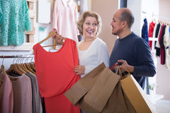 Mature couple choosing new apparel. In clothing shop Stock Image