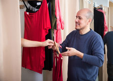 Mature couple choosing new apparel. Happy mature couple choosing new apparel in clothing store Royalty Free Stock Images