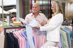 Mature couple in clothing store, holding shirt, smiling Royalty Free Stock Images