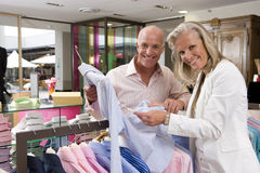 Mature couple in clothing store, holding shirt, smiling, portrait Stock Photo