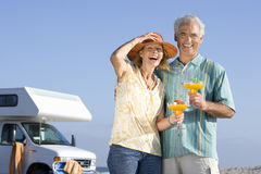 Mature couple with cocktails by motor home on beach, smiling, portrait, low angle view Stock Photos