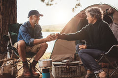 Mature couple with coffee camping by a lake. Portrait of senior women giving a cup of coffee to men at campsite. Both sitting outside tent. Mature couple camping royalty free stock photography