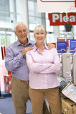 Mature couple in computer shop, smiling, portrait Stock Images
