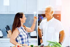 Mature couple cooking at home. Happy couple cooking together at home royalty free stock photos
